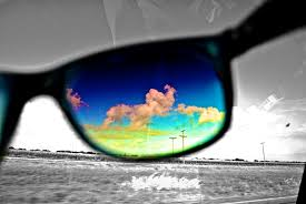 Coloured picture of clouds in the sky through a single sunglasses lens with a grey background